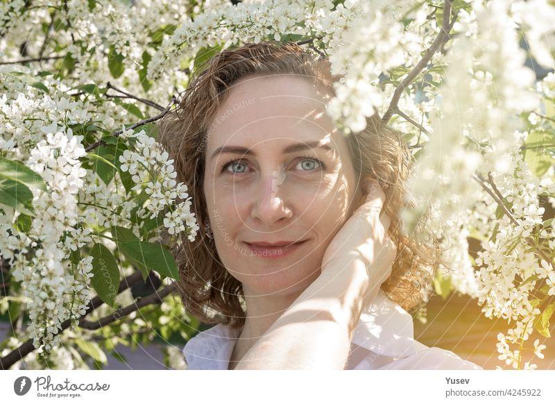 Schöne lächelnde kaukasische Frau mit lockigem Haar posiert unter einem blühenden Baum. Frühling Fotoshooting, sonniger Tag. Porträt einer glücklichen Frau. Frühlingssonne