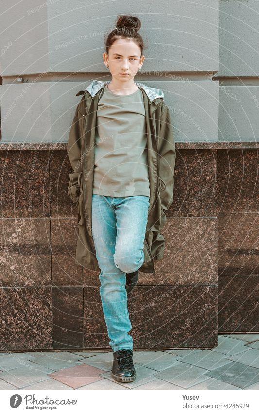 Junges nachdenkliches kaukasisches Mädchen lehnt an einer Industriewand. Full-lenght Porträt eines hübschen Modells in Freizeitkleidung. Straße Fotoshooting, Vorderansicht.