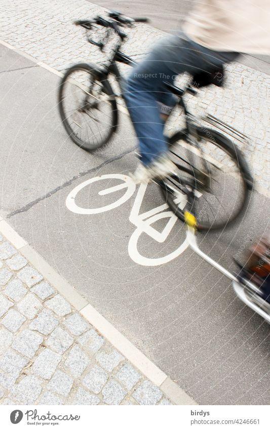 schnell vorbeifahrender Radfahrer mit Anhänger auf einem schmalen Radweg in der Stadt, Bewegungsunschärfe Radfahren Radwegsymbol Fahrradfahren Transport
