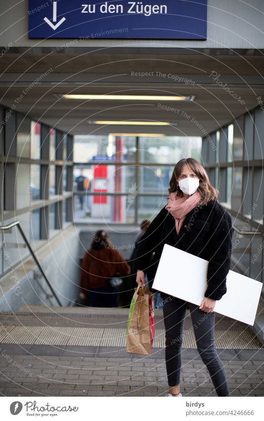schlanke junge Frau mit FFP2-Maske  und Gepäck auf dem Bahnhof. Zugreisende Corona-Virus Mundschutz Schützen COVID-19 ÖPNV Züge Pfeil Schilder & Markierungen