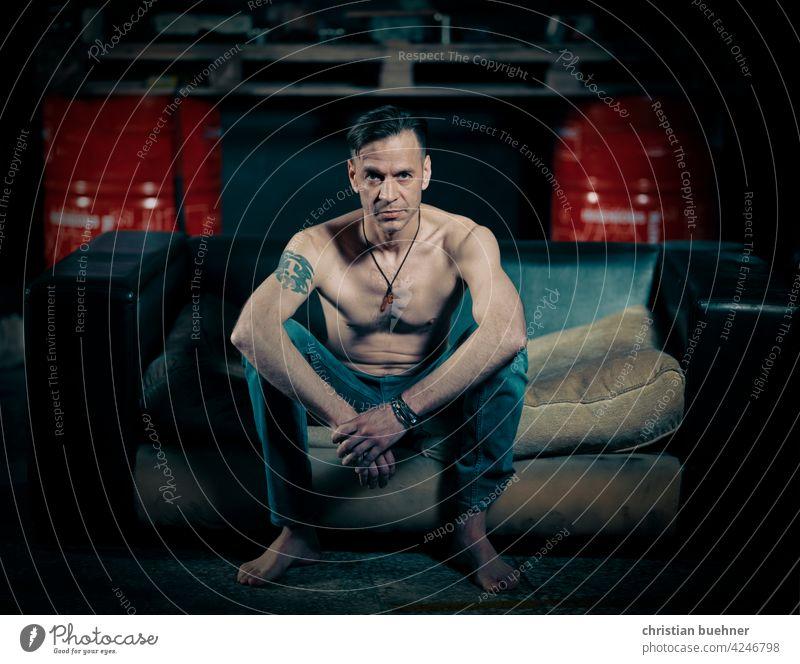 mann sitzt auf Sofa in der Autowerkstatt portrait nackt shirtless nackter oberkörper jeans barfuss autowerkstatt sofa schmuck cool werbung arbeit sexy erotisch