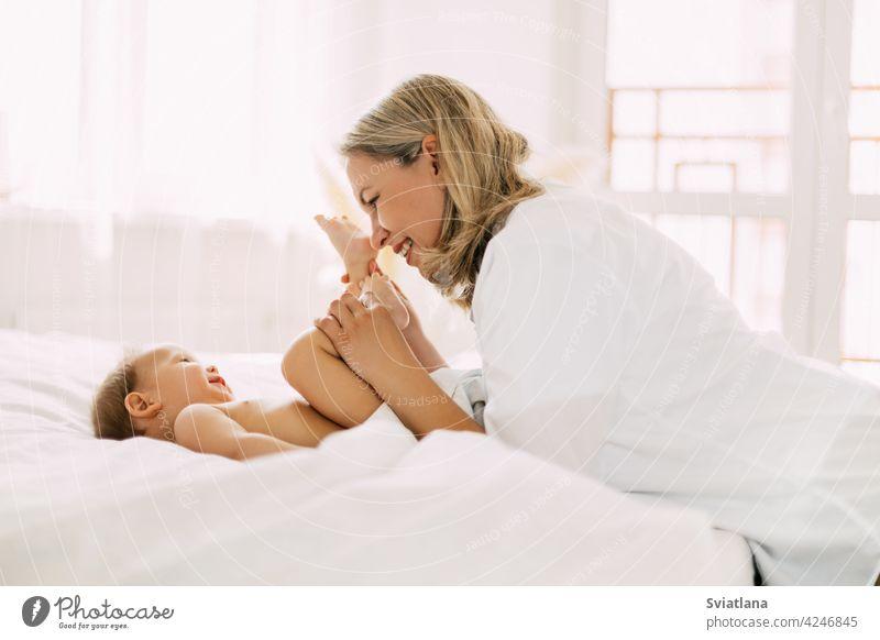 Glückliche Mutter spielt mit ihrem lächelnden Baby, küsst seine kleinen Füße. Pflege, Liebe, Kindheit, Mutterschaft. Seitenansicht, Platz für Text Säugling