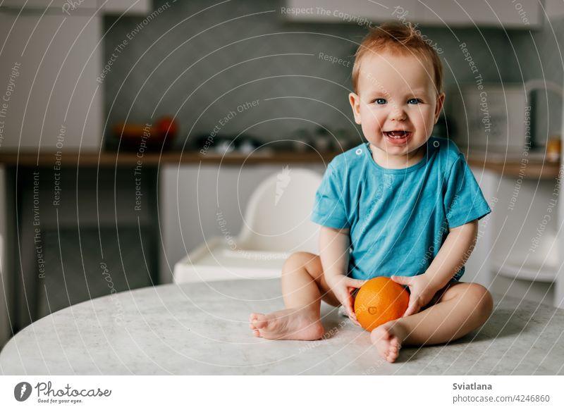 Ein kleiner Junge sitzt auf dem Küchentisch mit einer Orange in den Händen und lächelt wenig Baby orange Essen Kind Gesundheit Glück frisch Kleinkind niedlich