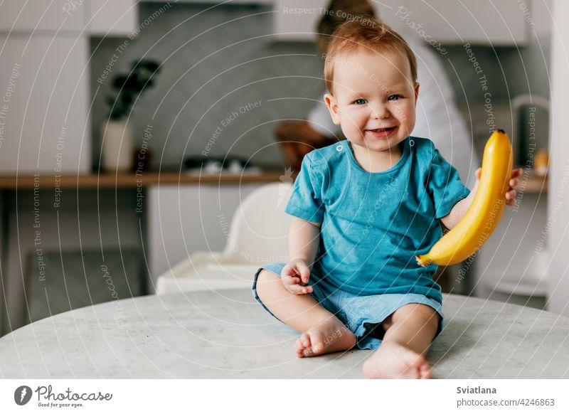 Ein kleiner Junge sitzt auf dem Küchentisch mit einer Banane in den Händen und lächelt Baby Lebensmittel Gesundheit Glück frisch Kleinkind niedlich Frucht