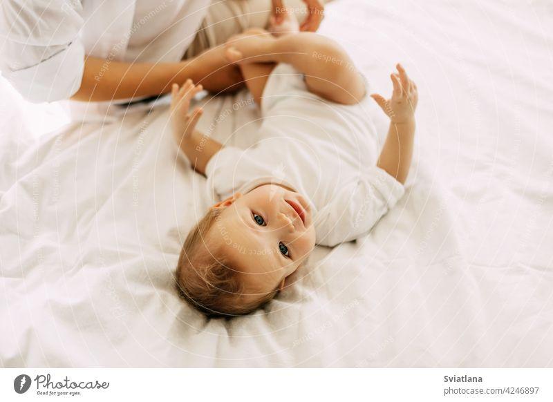 Ein charmantes Baby liegt mit seiner Mutter auf dem Bett, Mutter und Baby ruhen sich gemeinsam aus. Unschuld, Einigkeit und Familie Mama Lügen