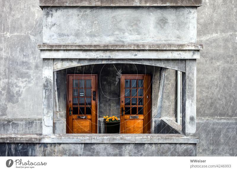 Warm wirkende Holztüren in einer grauen verwitterten Fassade, Serviervorschlag mit Blümchen Türen Haus Putz Eingang warm einladend hübsch trist Mehrfamilienhaus
