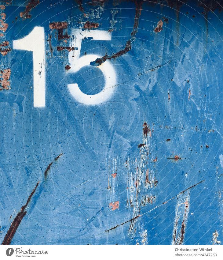 Eine weiße 15 auf der zerkratzten Metallwand eines viel genutzten alten blauen Containers Nummer Fünfzehn Zahl Ziffer Ziffern & Zahlen Metallfassade