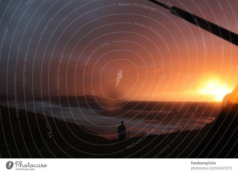 Blick aus einem Auto auf einen regenverhangenen Sonnenuntergang an einer Meeresbucht Sonnenuntergangshimmel Sonnenuntergangsstimmung Abenddämmerung Regen