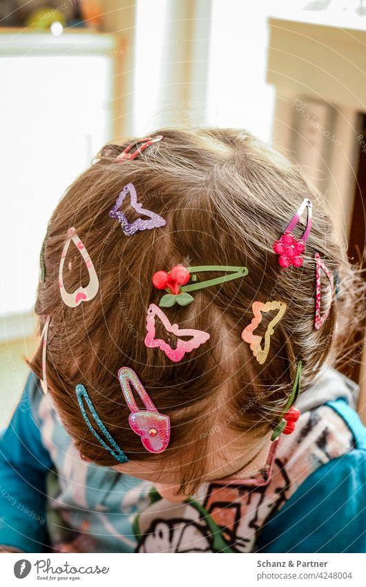 Kind mit ganz vielen Haarspangen im Haar Haare Frisur ausprobieren neugierig mädchen schmücken Schmuck Haarklammern Kindheit Familienleben Kinder spielen