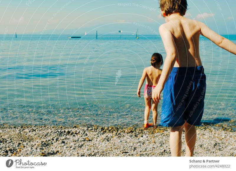 zwei Kinder am Strand Ferien & Urlaub & Reisen Geschwister Sommer Meer Schwimmen & Baden Wasser Kindheitserinnerung Sommerurlaub Badehose Farbfoto Außenaufnahme
