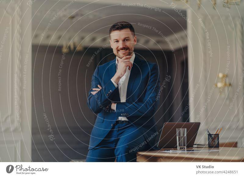 Porträt von lächelnden zuversichtlich Geschäftsmann sitzt auf Büro Schreibtisch Lächeln Mann Laptop Business gutaussehend Blick Glück selbstbewusst positiv