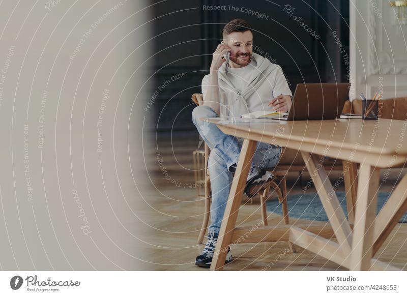 Junger lachender Mann Freiberufler, der am Handy spricht, während er an seinem Arbeitsplatz zu Hause sitzt und aus der Ferne am Laptop arbeitet Geschäftsmann
