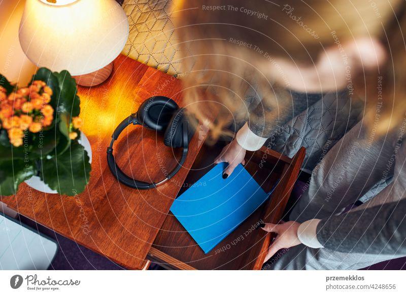 Junge Frau holt Tagebuch aus Nachttischschublade. Tagebuch schreiben Bildung im Innenbereich Lernen Schüler Person Hinweis Notebook studierend Buch Handschrift