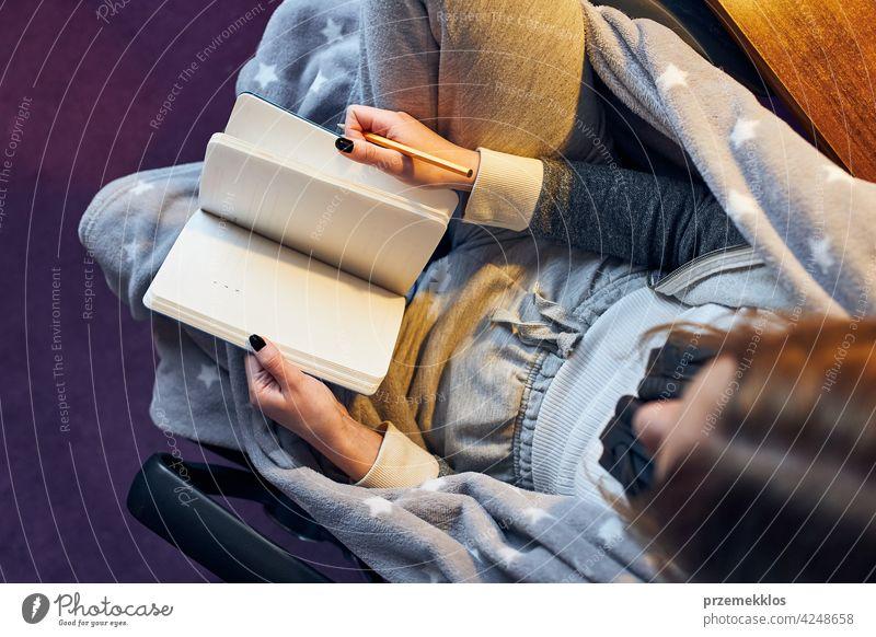 Schüler beim Lernen zu Hause. Junge Frau macht sich Notizen, liest und lernt vom Notizblock Bildung im Innenbereich arbeiten Person Hinweis Notebook studierend