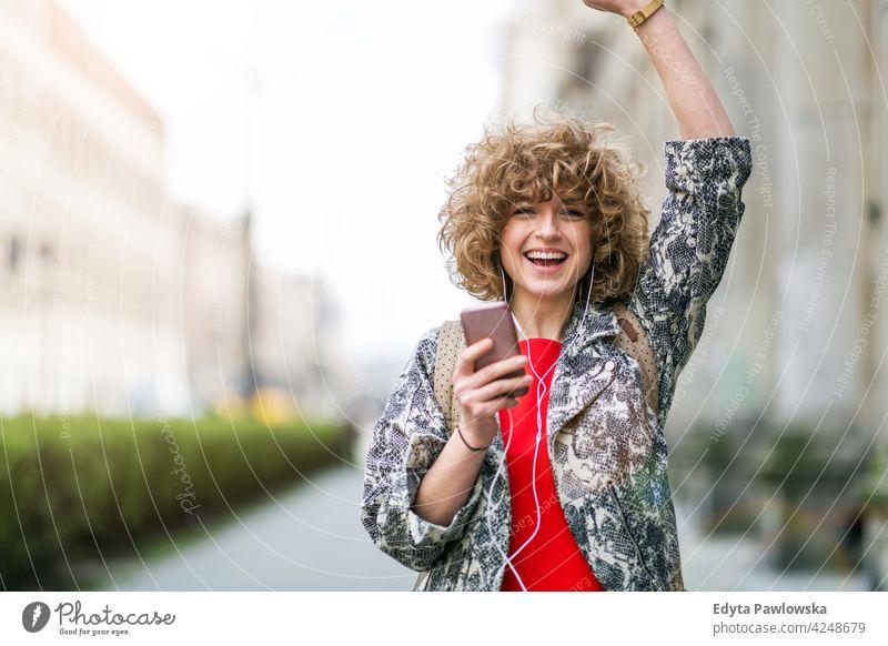 Junge Frau genießt Musik im Freien genießend Lifestyle jung Erwachsener Menschen eine Person lässig Kaukasier positiv sorgenfrei Glück Lächeln attraktiv schön