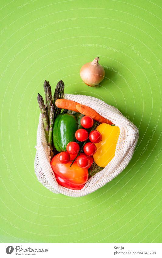 Frisches rohes Gemüse in einer wiederverwendbaren Einkaufstasche auf einem grünen Hintergrund. Draufsicht. Einkaufsnetz Wiederverwendbar grüner Hintergrund