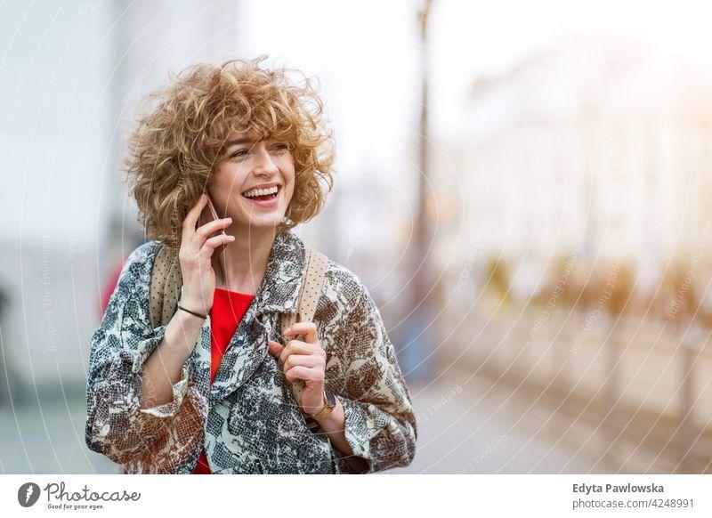 Porträt einer jungen Frau, die ein Mobiltelefon benutzt genießend Lifestyle Erwachsener Menschen eine Person lässig Kaukasier positiv sorgenfrei Glück Lächeln