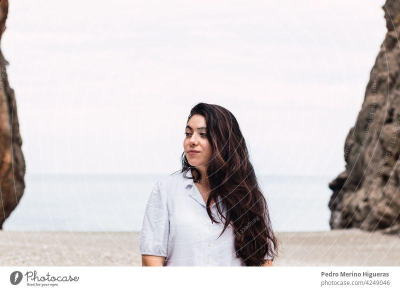 schöne Frau weiß gekleidet in einem Kieselstein Strand Kieselsteine Mädchen Natur Hintergrund im Freien reisen natürlich Klippe Himmel Kaukasier Urlaub Wasser