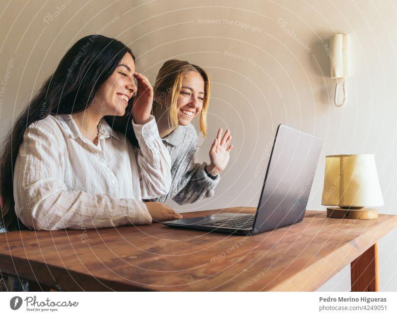 zwei Frauen Freunde winken, während auf Videoanruf Laptop Lifestyle Internet Sitzen Computer Glück Zusammensein Paar Liebe heimwärts jung online