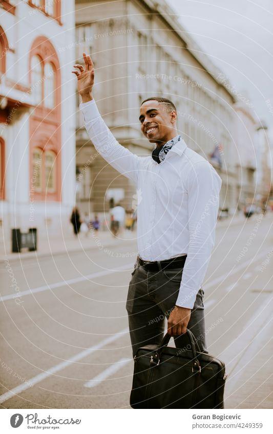 Junger afroamerikanischer Geschäftsmann wartet auf der Straße auf ein Taxi Amerikaner schwarz Gebäude Business Kabine kausal Großstadt Stadtzentrum ethnisch Typ