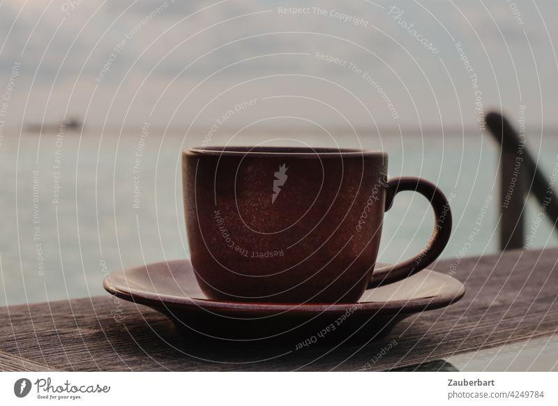 Eine dunkelbraune Tasse steht auf einem Holztisch vor dem Meer, Entspannung und Ruhe, in gedeckten Farben Tisch Tee Kaffee Blick Horizont friedlich Genuss