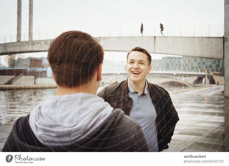 zwei männliche Teenager Freunde, die ein lustiges Gespräch am Fluss führen reden unterhalten Lachen Spaß authentisch Lifestyle echte Menschen Jugendliche Mann