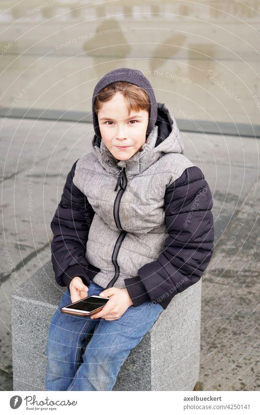 7 Jahre alter Junge mit Smartphone im Freien im Winter Kind spielen Technik & Technologie Spiel Internet Lifestyle jung Kindheit Person Kaukasier Drahtlos