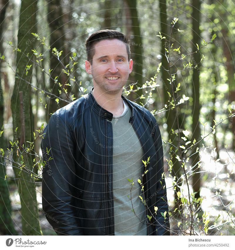 Ein junger Mann in Wald, neben einem dünnen Strauch mit kleine , hell grünen Blätter die von der Sonne beleuchtet werden. mann sportlich natur liebe blaue augen
