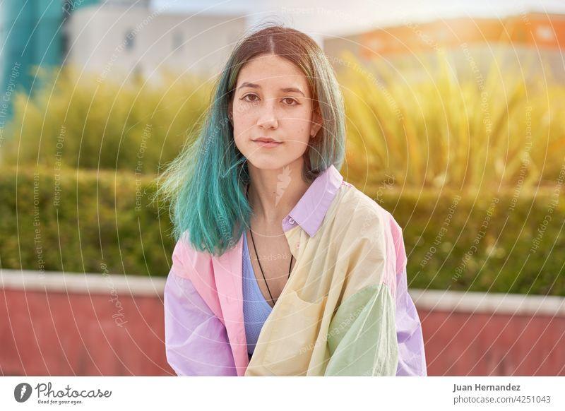junges Mädchen mit türkisfarbenen Haaren sitzt und schaut in die Kamera Kaukasier Behaarung Sitzen in die Kamera schauen Blick besinnlich Denken Ausdruck