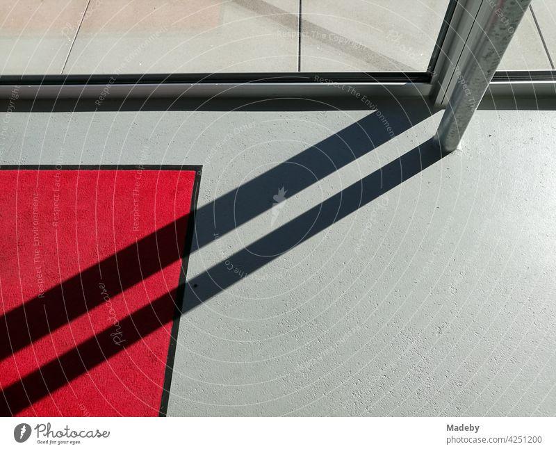 Diagonaler Schatten auf grauem Boden und rotem Teppich im Eingangsbereich einer Galerie in moderner Architektur in Oelde in Westfalen Licht Sonnenschein Grau