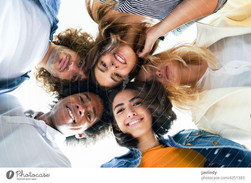 Multi-ethnische Gruppe von Freunden, die ihre Köpfe in einem Kreis zusammenstecken. Menschen jung multiethnisch Menschengruppe rassenübergreifend Vielfalt