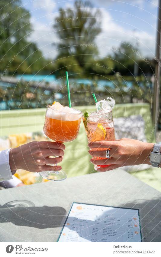 Zwei Menschen jubeln mit rosa Cocktails draußen auf einer Terrasse an einem sonnigen Tag mit Schwimmbad im Hintergrund jubelt Hände trinken Essen und Trinken