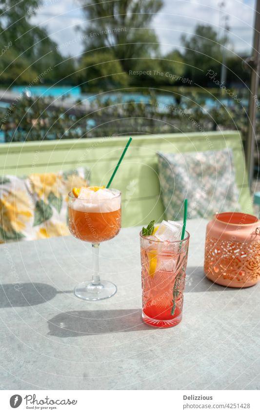 Pinke Cocktails, die draußen auf einer sonnigen Terrasse mit Swimmingpool im Hintergrund serviert werden trinken jubelt Essen und Trinken Genießer Bar Sommer