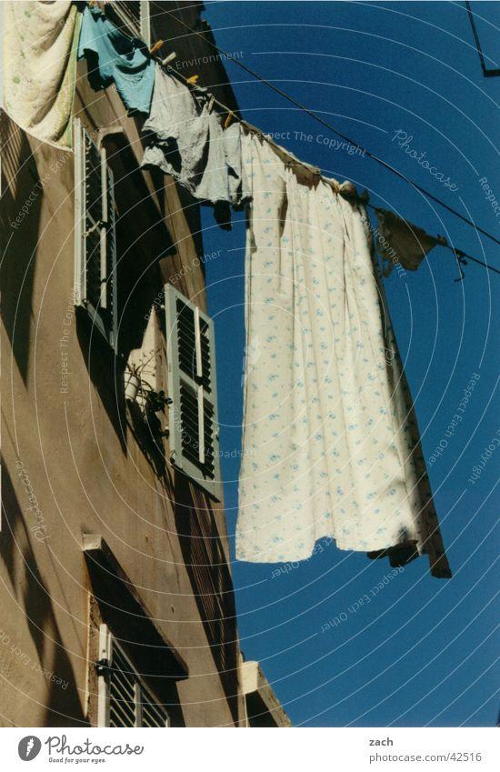 Wäscheleinenzwang Farbfoto Außenaufnahme Menschenleer Tag Froschperspektive exotisch Häusliches Leben Haus Seil Himmel Korfu Griechenland Fenster Bekleidung