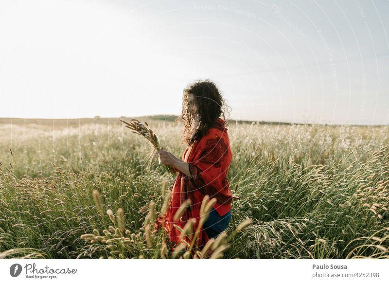 Frau pflückt Blumen Frühling Kommissionierung Blumen pflücken Kaukasier authentisch Feld Wiese Erwachsene Garten grün Natur Außenaufnahme Umwelt rot Ernte Hand