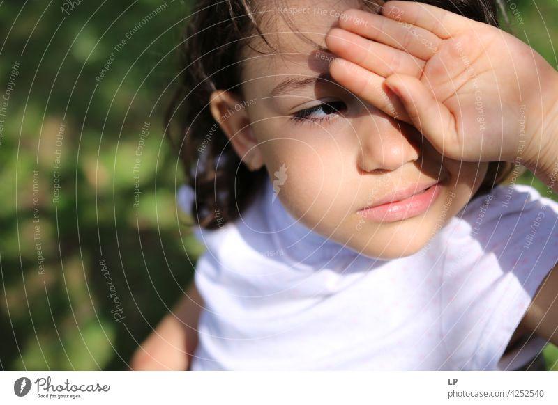 neugieriges Mädchen schaut in die Sonne und schützt ihre Augen mit der Hand zuschauend Überraschung spielerisch Person Blick Aussehen Lernen Kind Gesicht