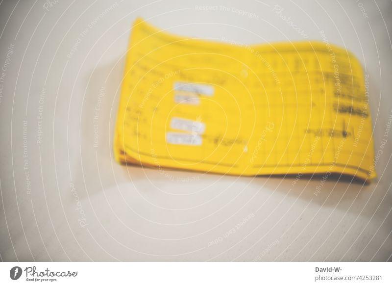 Impfpass / Impfausweis auf einem Tisch gelb Impfung coronavirus Schutz Gesundheit Risiko Pandemie geimpft Impfpflicht