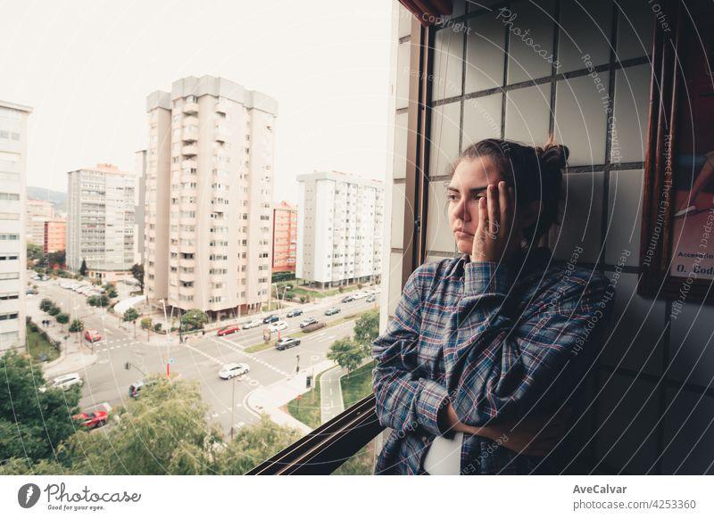 Besorgte Frau, die aus dem Fenster ihrer Wohnung schaut, Konzept der psychischen Gesundheit in der Stadt, Depression mit Kopierraum Angst Frustration