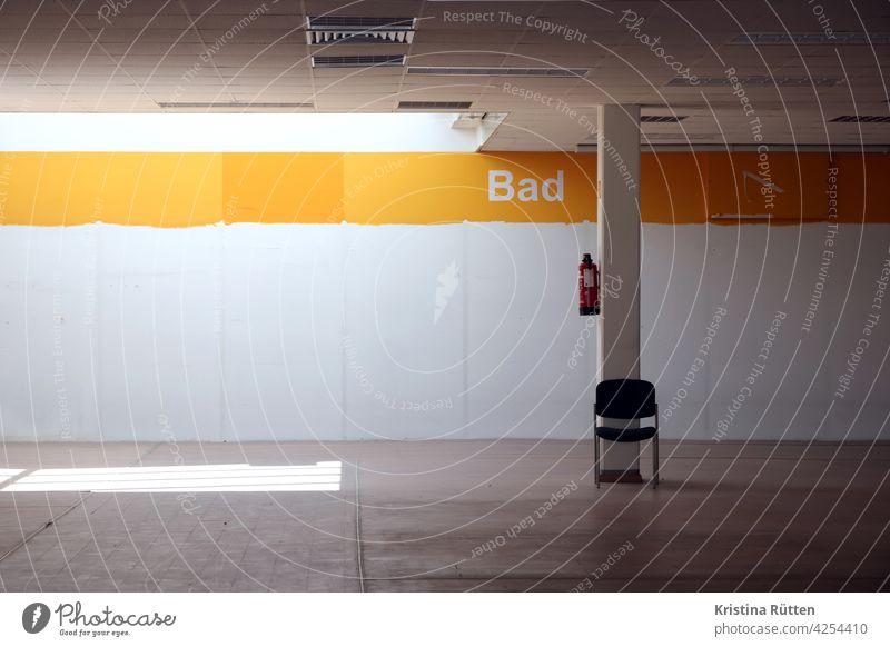 ein einzelner stuhl und ein feuerlöscher im leergeräumten ladenlokal bad verlassen ausgeräumt gschlossen leerstand raum schrift wand beschriftung kaufhaus