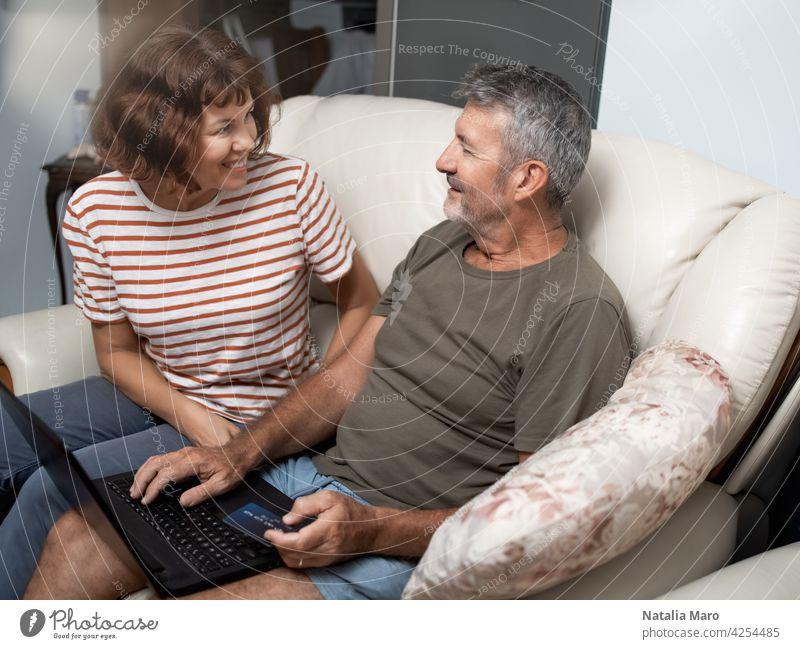 Lächelnde mittleren Alters Paar sitzt auf ihrer Couch mit dem Laptop zu Hause online kaufen Familie Frau Computer Mann Elektronischer Geschäftsverkehr Internet