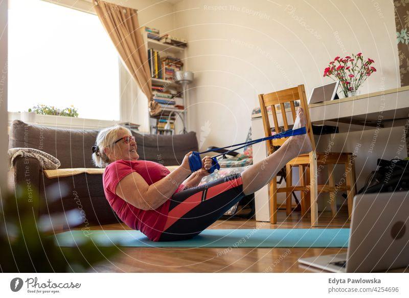 Ältere Frau trainiert zu Hause Brille Falte natürlich echte Menschen lässig Tag Lifestyle Großmutter Rentnerin gealtert Freizeit Ruhestand Lebensalter