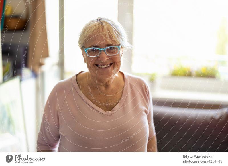 Glückliche ältere Frau lächelnd zu Hause Brille Falte natürlich echte Menschen lässig Tag Lifestyle Großmutter Rentnerin gealtert Freizeit Ruhestand Lebensalter