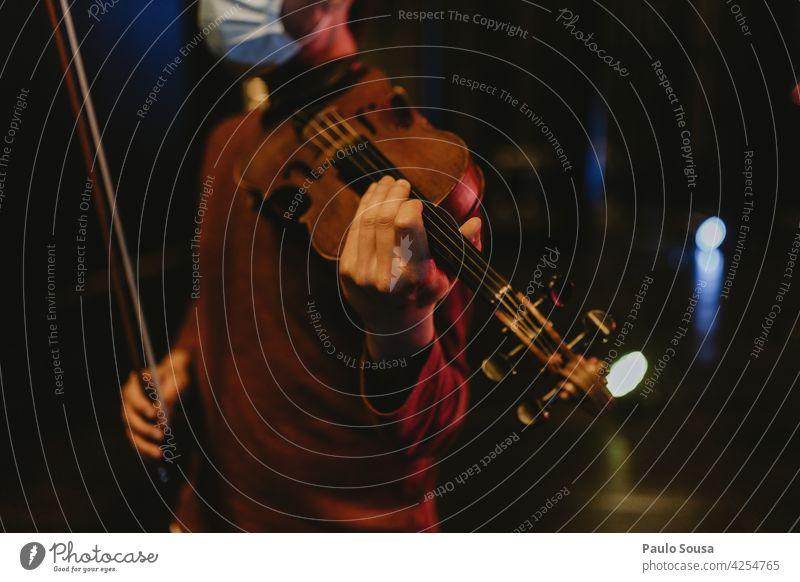 Mann mit Gesichtsmaske hält Geige Geiger Musik Musiker Instrument Klassik Farbfoto Schleife Kunst Konzert klassisch Musik hören Nahaufnahme musizieren Klang