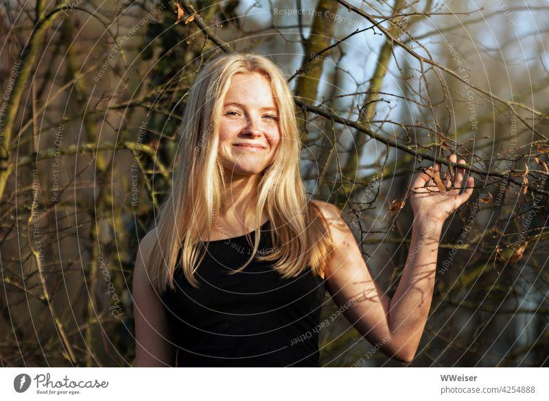 Ein lachendes blondes Mädchen spielt mit den Zweigen eines Baumes und freut sich über die  Sonne im Wald hübsch attraktiv fröhlich heiter lächeln froh glücklich
