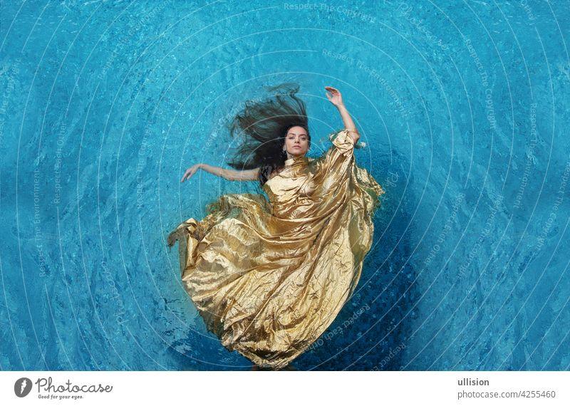 schöne junge Frau in goldenem Kleid, Abendkleid schwebt schwerelos elegant im Pool schwimmend Wasser attraktive Frau sonnig Textfreiraum Platz für Text stolz