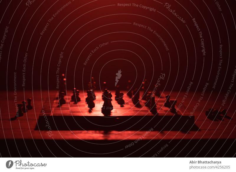 Schachbrett mit Schachfiguren Holzplatte Tisch Stillleben Teile dunkel Schatten rot Licht Farbe Objekte Heiligenschein Spielen Pferd König Bauer Läufer Verstand