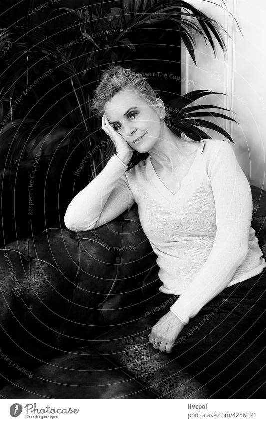 Frau ruhend auf Chester-Sofa II blond Menschen chester schwarz auf weiß Schatten Blumen gelb Kaffee trinken Innenbereich lokal Kaffeehaus Kantine Szene Licht