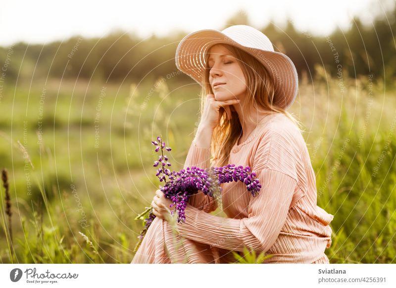 Porträt einer schönen Blondine mit einem Strauß Lupinen in den Händen auf dem Rasen sitzend Mädchen Feld Blumenstrauß Hut Sommer ein Blumenstrauß aus Lupinen