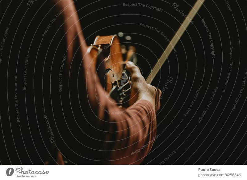Nahaufnahme Hand hält Geige Geiger Musikinstrument Konzert Klassik Instrument Musiker Farbfoto Kunst Schleife Cello Schauplatz musizieren Streichinstrumente