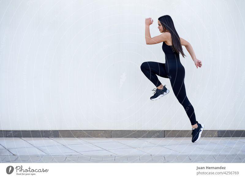 Junge Frau mit fit Körper springen und laufen jung passen springend rennen Model Sportbekleidung trainiert. Athlet Übung Fitness Training Läufer horizontal